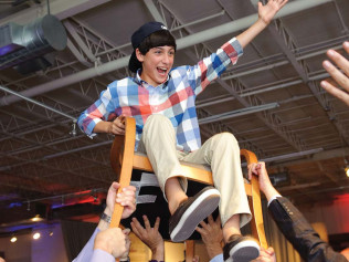 A boy turning 13 in a chair at his bar mitzvah in Wilmington, DE