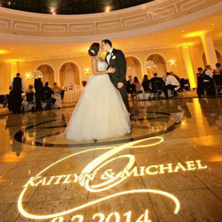 Photo of a bride and groom dancing their first dance with monogrammed dance floor in Wilmington, DE